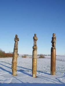 Sculptures in wood at the entrance of the village