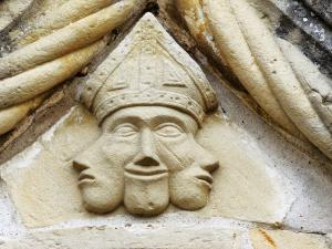 Three-headed sculptured mask, above the portal of the church (© J.E)