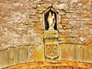 Virgin and shield above the door of the big farm building in the lower courtyard (© Jean Espirat)