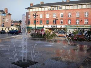 Abbeville - Square featuring a fountain and jets, rosebushes, shops and buildings of the city