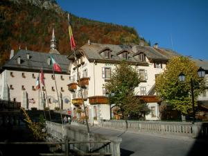 Abondance - Bridge with flags, house (mansion) of the village (ski resort), abbey and bell tower of the Notre-Dame-d'Abondance abbey church, forest in autumn in Haut-Chablais