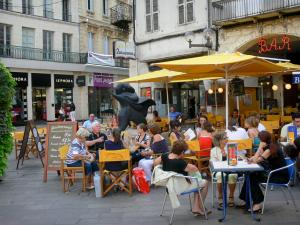 Agen - Place des Laitiers square: café terrace, statue of pilgrim St James de Compostela, shops and facades of houses in the old town
