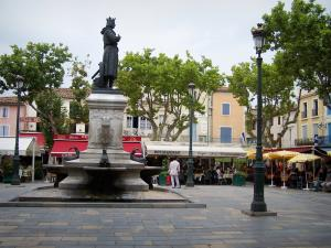 Aigues-Mortes - Place Saint-Louis square: statue of St. Louis, fountain, lampposts, restaurant terraces, plane trees and facades of houses