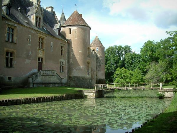 Ainay-le-Vieil castle - Moats with water lilies, medieval surrounding wall of the fortress and trees