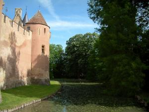 Ainay-le-Vieil castle - Trees, moats with water lilies and tower of the feudal surrounding wall