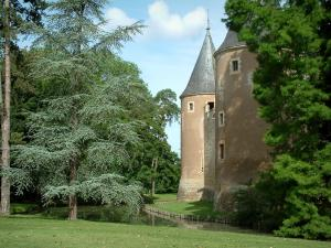 Ainay-le-Vieil castle - Trees, moats and towers of the feudal surrounding wall