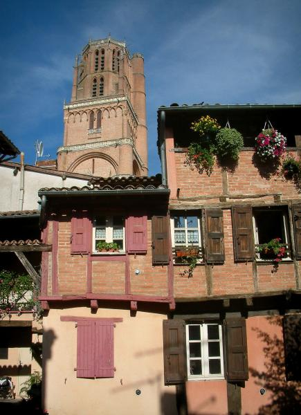 Albi - Brick-built house decorated with flowers and bell tower of the Sainte-Cécile cathedral