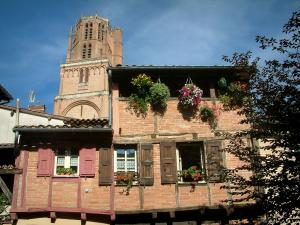 Albi - Brick-built timber-framed house, flowers, and bell tower of the Sainte-Cécile cathedral
