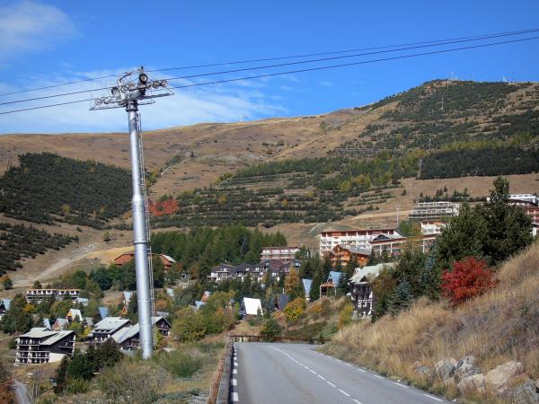 L'Alpe d'Huez - Road, ski lift, chalets and buildings of the winter and summer sports resort (ski resort) in autumn, mountains dotted with trees and grass