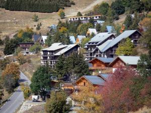 L'Alpe d'Huez - Road, trees and chalets of the winter and summer sports resort (ski resort) in autumn