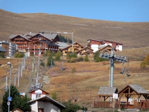 L'Alpe d'Huez - Winter and summer sports resort (ski resort): chalets, ski lifts and grassland in autumn