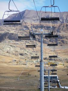 L'Alpe d'Huez - Winter and summer sports resort (ski resort): chair lift, grasslands and mountains in the background, in autumn
