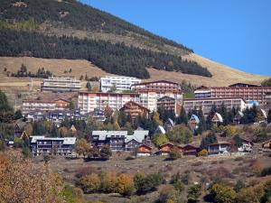 L'Alpe d'Huez - Buildings and chalets of the winter and summer sports resort (ski resort), trees and grasses in autumn