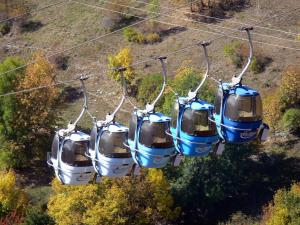 L'Alpe d'Huez - Cable car (ski lift) of the winter and summer sports resort (ski resort), trees down below with autumn colors