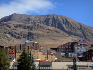 L'Alpe d'Huez - Buildings of the winter and summer sports resort (ski resort), mountain overhanging the place
