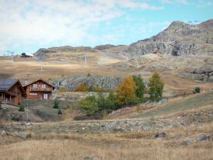 L'Alpe d'Huez - Chalets, ski lift of the winter and summer sports resort (ski resort), grasses and trees with autumn colors