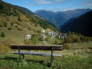 Alps landscapes in the Savoie - Wooden bench with view of alpine pastures, houses of a village, trees in autumn, forests and mountains