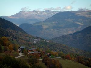 Alps landscapes in the Savoie - Trees with autumn colours, mountain villages and mountains covered with forests
