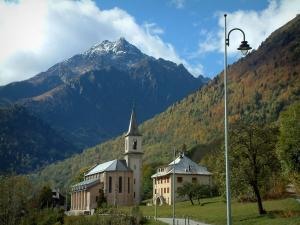 Alps landscapes in the Savoie - Lamppost, church and houses of a village, a forest in autumn, mountain and clouds in the sky