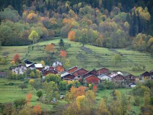Alps landscapes in the Savoie - Chalets of a mountain village, alpine pastures and trees with autumn colours