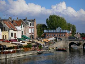 Amiens - Saint-Leu district: small houses, restaurant and cafe terraces along the water, bridge spanning the canal, clouds in the sky
