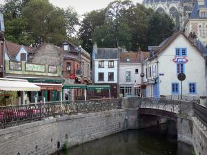 Amiens - Saint-Leu district: houses, cafe terraces along the water, small bridge spanning the canal and cathedral in background