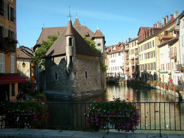 Annecy - Flower-bedecked  bridge with view of the Île palace (former prison) home to the Annecy History museum, Thiou canal and its water birds, Île quayside and houses with colourful facades in the old town