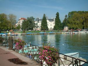 Annecy - Flower-bedecked shore of the Europe gardens with view of Lake Annecy, boats, pedal boats, the Champs de Mars, trees and buildings of the city