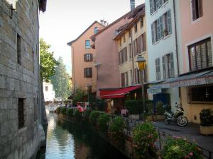 Annecy - Île Palace (former prisons), the Thiou canal, flower-bedecked bank, restaurants and houses with colourful facades