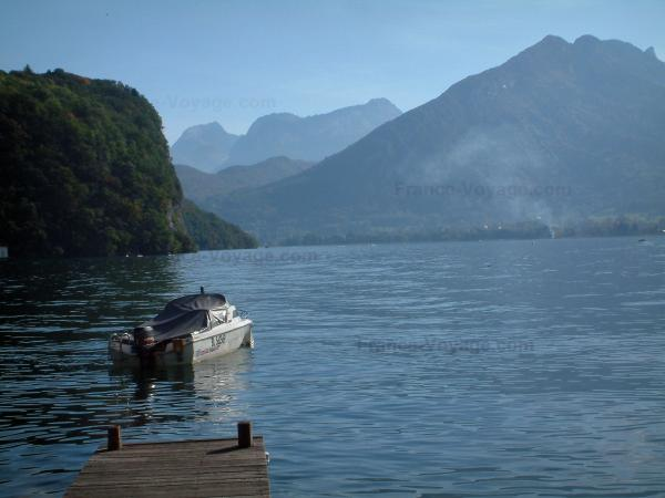 Annecy lake - Wooden pontoon, lake, motorboat and mountains covered with forests