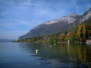Annecy lake - Lake, yellow buoys, trees with autumn colours, houses, forest and mountain
