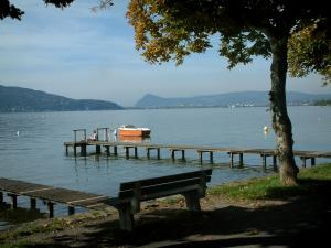 Annecy lake - Shore with a bench and a tree, lake, wooden pontoons, boat and hills in background