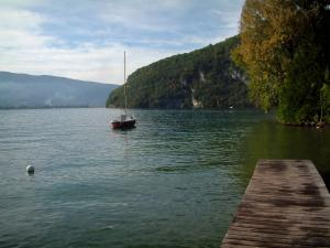 Annecy lake - Wooden pontoon, lake, sailboat, trees and hills covered with forests