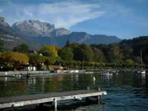 Annecy lake - Wooden pontoon, lake, boats, trees with autumn colours and mountains