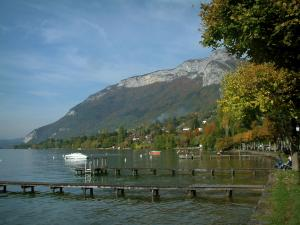 Annecy lake - Lake, wooden pontoons, boats, shore, trees with autumn colours, houses, forest and mountain