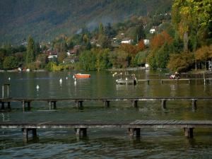 Annecy lake - Lake with wooden pontoons, boat and buoys, houses, trees and forest in autumn
