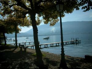 Annecy lake - Bench and trees on the shore with view of the lake and its wooden pontoons, boats, buoys and hills