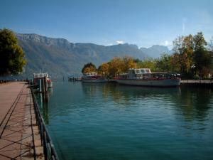 Annecy lake - In Annecy: quai Napoleon III (quayside), jetty (port) with moored boats, trees with autumn colours, lake and mountains in background