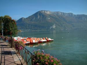 Annecy lake - In Annecy: flower-bedecked shore, moored pedal boats, lake and mount Veyrier