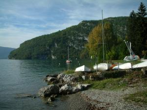 Annecy lake - In Talloires: beach, cliffs, lake, sailboats, trees in autumn and hill