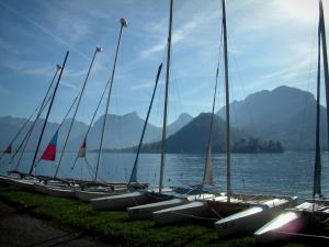 Annecy lake - In Talloires: catamarans lined up on the shore with view of the lake and mountains
