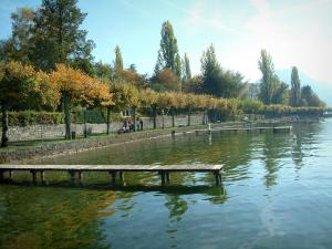Annecy lake - Wooden pontoons of the lake, shore, and trees with autumn colours