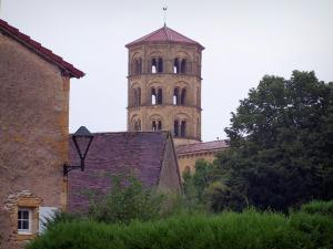 Anzy-le-Duc - Octagonal bell tower of the Notre-Dame-de-l'Assomption church of Romanesque style, houses of the village and trees; in Brionnais