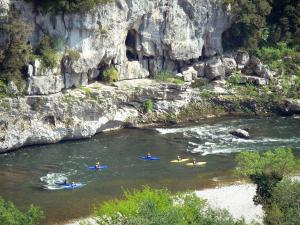 Ardèche gorges - Kayaking on the waters of the Ardèche; rock wall overlooking the river