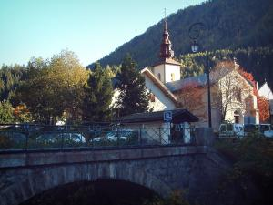 Argentière - Bridge, trees, the Saint-Pierre Baroque church with its bell tower, houses of the village (ski resort) and forest
