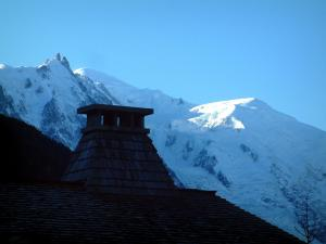 Argentière - Roof and chimney of a house of the village (ski resort) with view of the snowy Mont Blanc mountain range