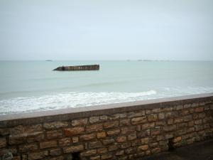 Arromanches-les-Bains - Stone low wall in foreground, the Channel (sea), and the remains of the artificial port