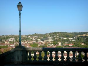 Auch - Lamppost and railing of the monumental staircase in the foreground, view of the Gers valley and the rooftops of the lower town