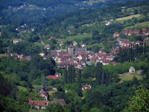 Autoire - View of the houses of the village, trees and prairies, in the Quercy