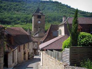 Autoire - Street lined with houses, church bell tower and trees, in the Quercy